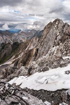 Вдали обнаженные скалы и горы, на переднем плане - остатки старого снега. видны слои в старой породе. облачная погода. вертикальный.