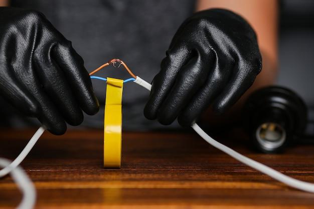 Голые провода изолирует изолентой человек в рабочих перчатках. подключение двух проводов. фото высокого качества