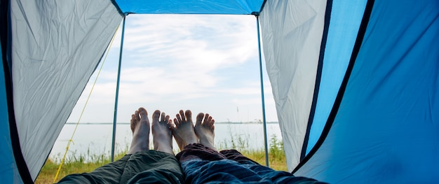 Bared legs of man and woman stretched out of tourist tent. view on river bank with green grass and blue sky on sunny summer day. crossed barefoot of lovers touching. family tourism, honeymoon.