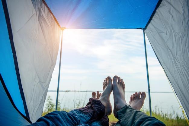 남자와 여자의 벌거 벗은 다리가 관광 텐트 밖으로 뻗어 있습니다. 화창한 여름날 푸른 잔디와 푸른 하늘이 있는 강둑에서 볼 수 있습니다. 맨발로 건넜던 연인들의 발길을 건넜다. 가족 여행, 신혼 여행.