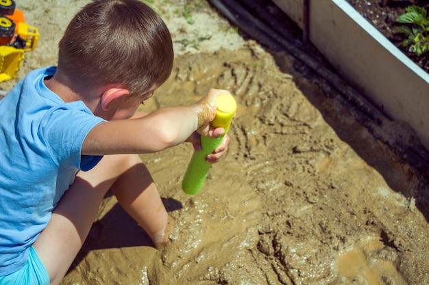 濡れた砂と水鉄砲で遊んでいるbarefeetの子供。小さな男の子は夏の晴れた日に泥をこねてモデル化します。