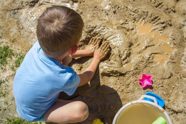 濡れた砂で遊んでいるbarefeetの子供。小さな男の子は夏の晴れた日に泥をこねてモデル化します。