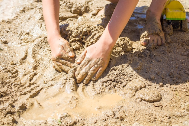 Barefeet kid playing with wet sand. little boy kneads and models mud on summer sunny day.