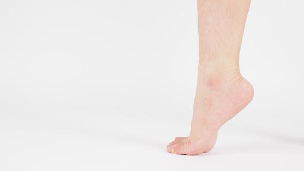アジア人男性の裸足と脚は白い背景で隔離されます。