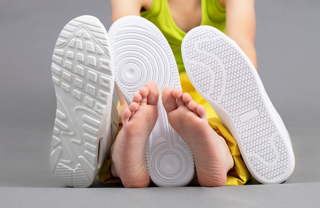 Barefoot on the background of shoes. feet in a pile of shoes. children's foot on the background of sneakers. foot and shoes