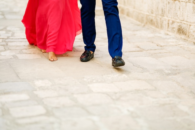 Barefoot bride in a long bright pink dress and the groom walking along a cobbled road closeup