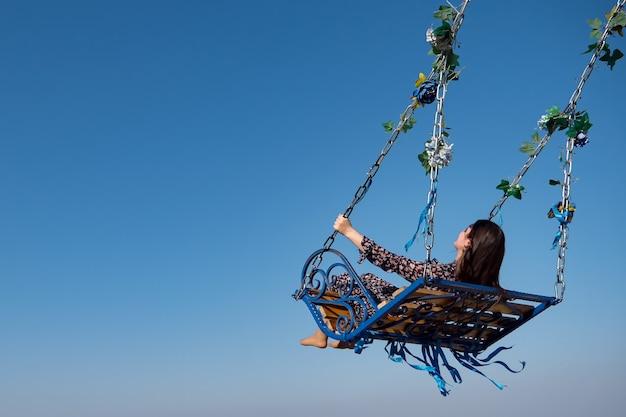 긴 폴카 도트 드레스를 입은 맨발의 브루네트는 푸른 하늘 아래 녹색 잎과 컬러 테이프로 장식된 대형 디자인 그네에 앉아 있습니다.