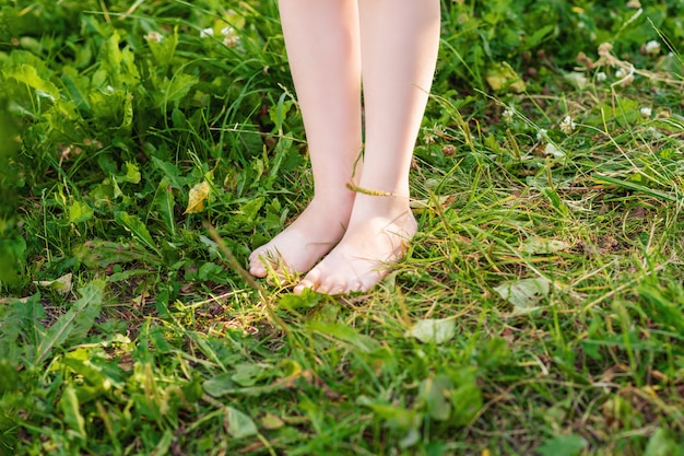 Barefoot of child standing on green grass