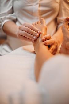 맨발의 고객이 전문 스파 살롱에서 다리 마사지 세션을 받고 있습니다.