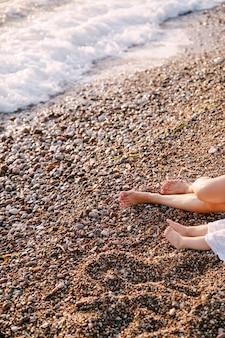 泡立つ海のそばの小石のビーチで裸足の女性と子供の足