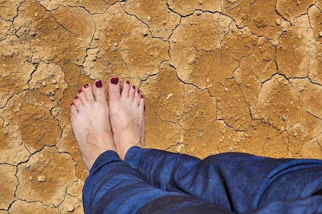 청바지에 맨발의 여성 발은 마른 금이 간 점토 토양에 서 있습니다