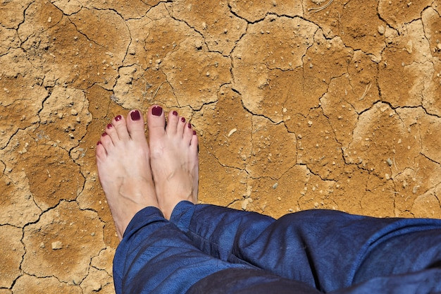 Barefoot female feet in jeans stand on dry cracked clay soil