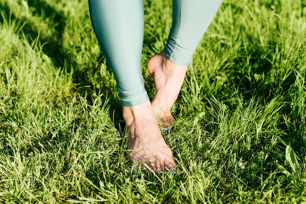 Босиком женские ноги на зеленой траве в природе женщина идет на зеленой лужайке на открытом воздухе крупным планом