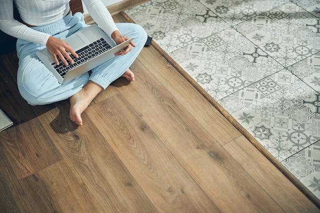 Босиком женщина-фрилансер сидит со своим компьютером на полу кухни