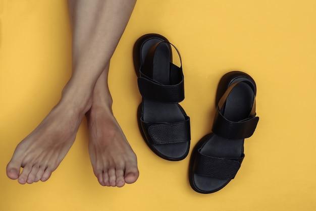 裸足の女性の脚と黄色の背景に革のサンダル。上面図