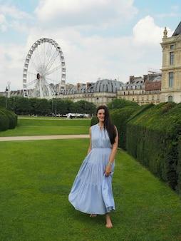 公園の緑の芝生の上を歩く長い青いドレスを着た裸足の女の子