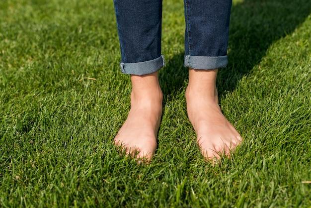 Barefoot little girl standing on grass close-up