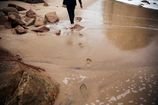 裸足の男が痕跡を残してビーチを歩いています