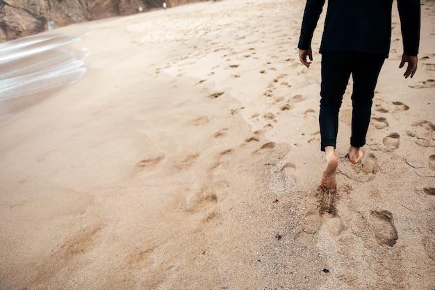 裸足の男が砂浜の上を歩いています。