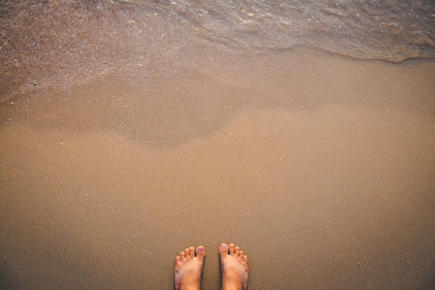 Barefoot stand on sand beach with wave