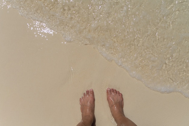 Barefoot stand on the sand at the beach