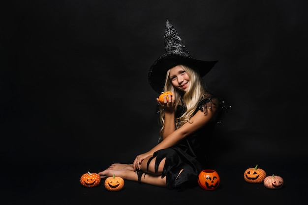 Barefoot witch amidst jack-o-lanterns