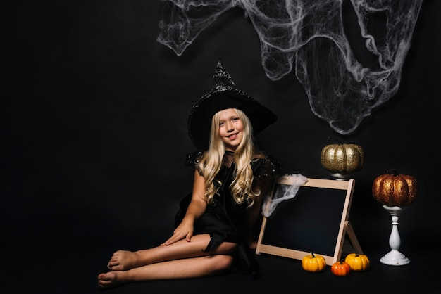 Barefoot witch near blackboard and halloween decorations