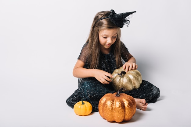 Barefoot witch playing with pumpkins