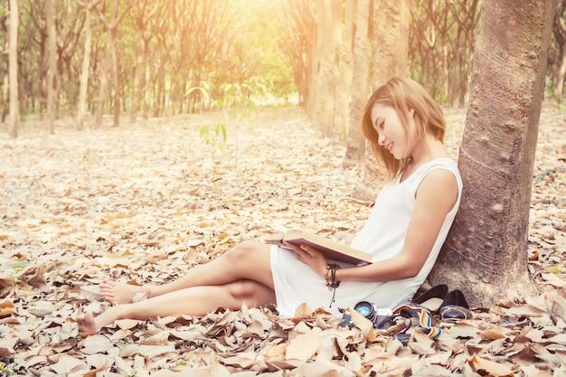 ベアフット女性が本を楽しみます