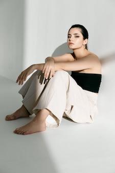 ファッショナブルな服を着た裸足の女性が明るい部屋の床に座っています