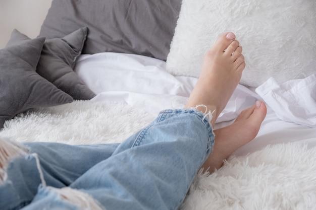 ベッドでリラックスしたジーンズの裸足の女性