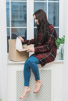Barefoot woman opening parcel