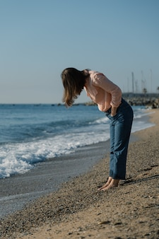 Barefoot woman in pink shirt and blue jeans looks down at her feet on beach