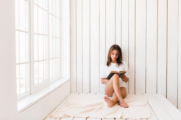Barefoot woman reading on blanket near window