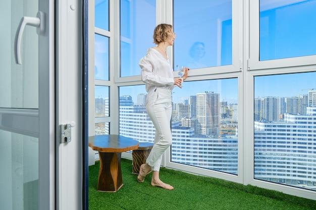 裸足の女性が新しいアパートのバルコニーに立ち、窓から街の景色を眺める