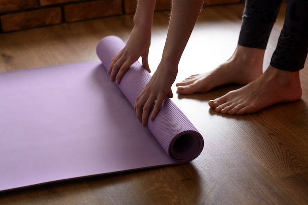 A barefoot woman twists a purple yoga mat and fitness on the parquet floor