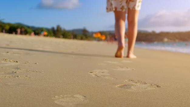Barefoot woman walks on ocean beach wet sand leaving footprints close up sunlight