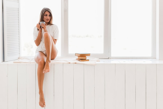 Barefoot woman with cup near window