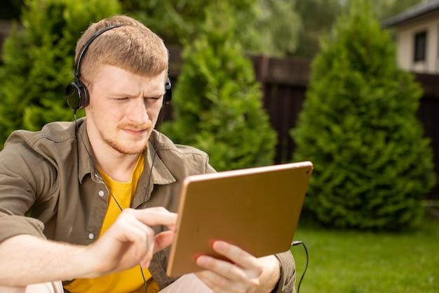 Босоногий молодой человек в желтых очках сидит на зеленой траве с планшетом, изучая иностранные языки или слушая музыку в наушниках.