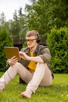 Босоногий молодой человек в желтых очках сидит на зеленой траве с планшетом, слушая музыку в наушниках.