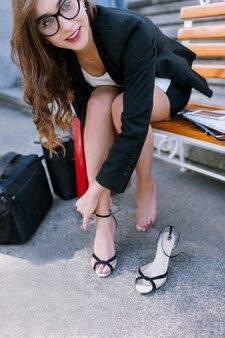 疲れた足を持つ裸足の若い女性。自信を持って抑制されていない女の子が靴を脱いで、現代の社会的行動