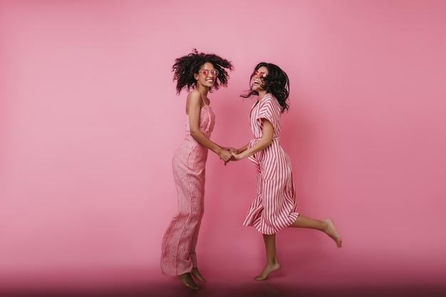 Ragazze castane a piedi nudi che ballano insieme e che guardano. ritratto di migliori amici in abiti rosa tenendosi per mano.
