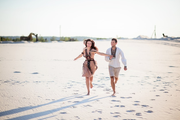 Barefooted couple in bright embroidered clothing runs on a white sand