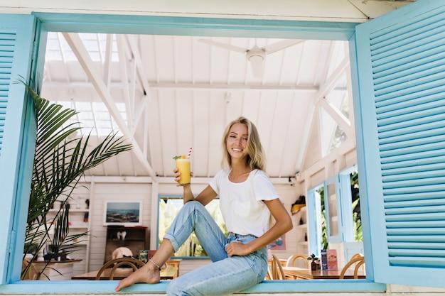 窓枠でカクテルを飲む裸足の女の子。魅力的な若い女性は素晴らしい笑顔でポーズをとる脚のブレスレットを身に着けています。