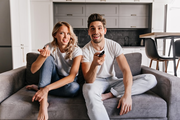 Barefooted lady in jeans watching tv. indoor portrait of couple relaxing on grey sofa.