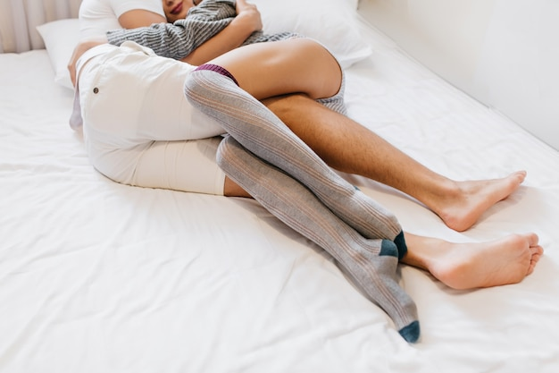 Barefooted man embracing wife while lying on white sheets in morning