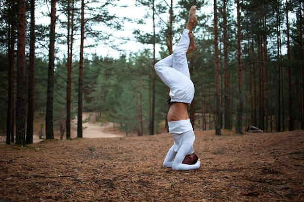 Barefooted young male in white clothes doing variation of salamba shirshasana yoga stance on ground in forest, crossing legs. outdoor shot of advanced yogi training in woods, balancing on hands