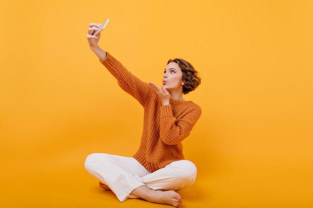 셀카를 만드는 동안 공기 키스를 보내는 스웨터에 맨발의 젊은 여자