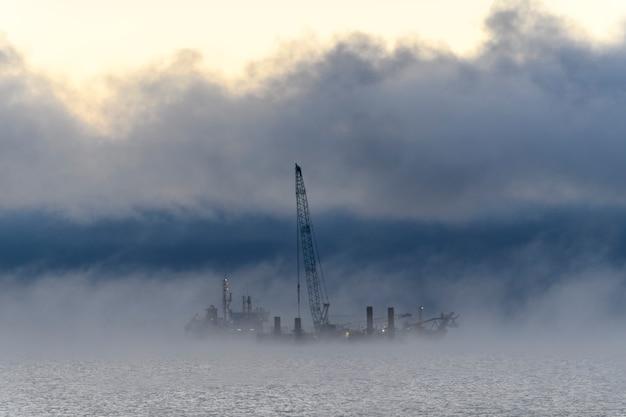 Баржа с краном. земснаряд работает в море. сильный туман в арктическом море. строительство морские морские работы. строительство плотины, кран, баржа, земснаряд.