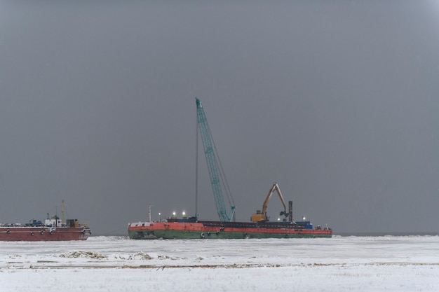 Barge with crane. dredger working at sea. strong fog in arctic sea. construction marine offshore works.